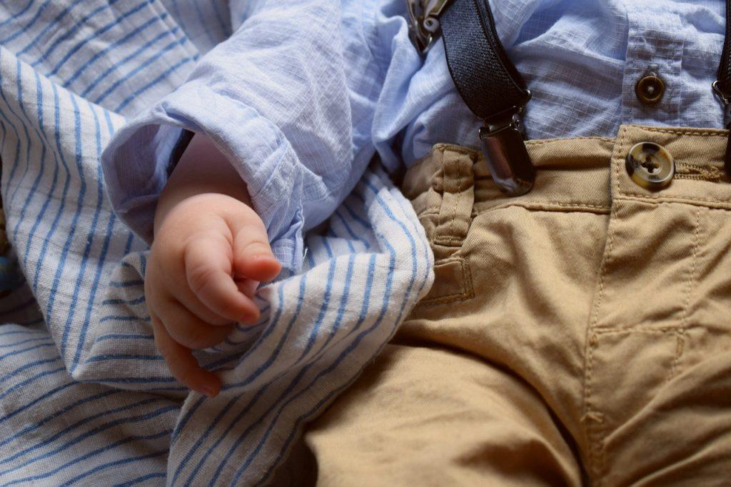 bébé qui porte une chemise bleu et un pantalon marron
